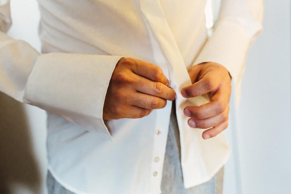 Bräutigam knöpft das Hemd zu beim Getting Ready