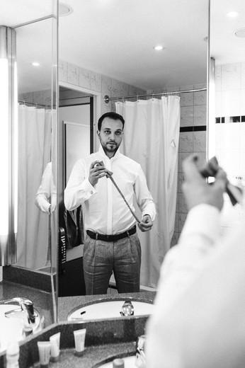 Bräutigam legt Krawatte vor dem Spiegel an