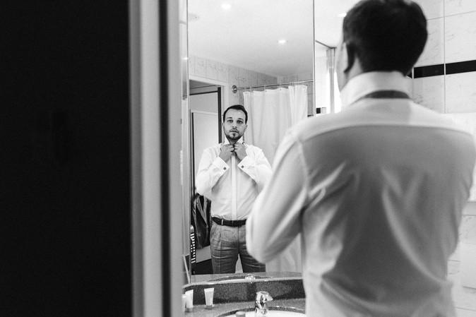 Bräutigam steht vor dem Spiegel