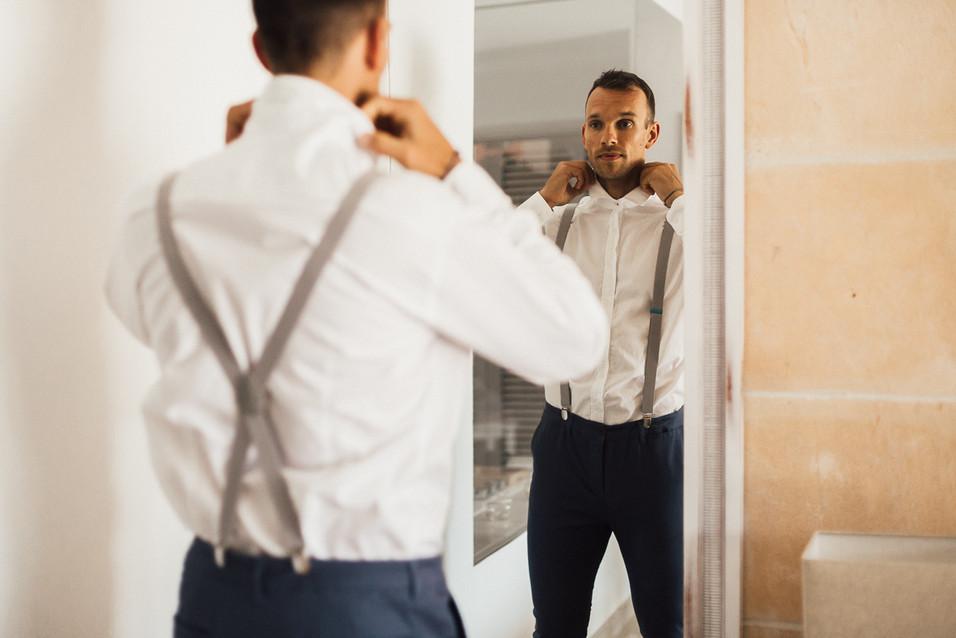 Bräutigam zieht sich vor dem Spiegel an