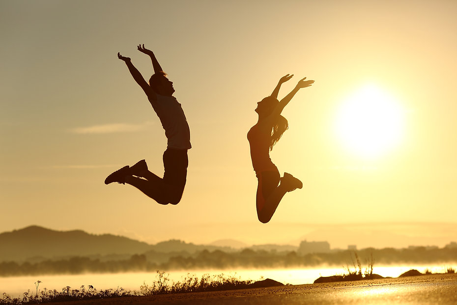 Fitness Couple Jumping Happy At Sunset.jpg