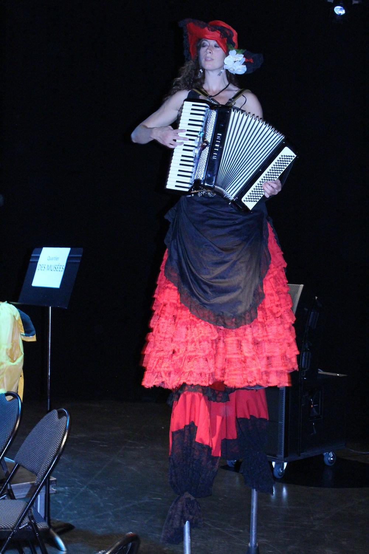 Élise du LaboKracBoom perchée sur des échasses, jouant de l'accordéon.