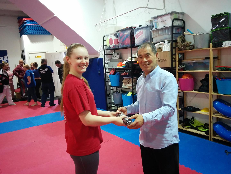 Receiving her black belt