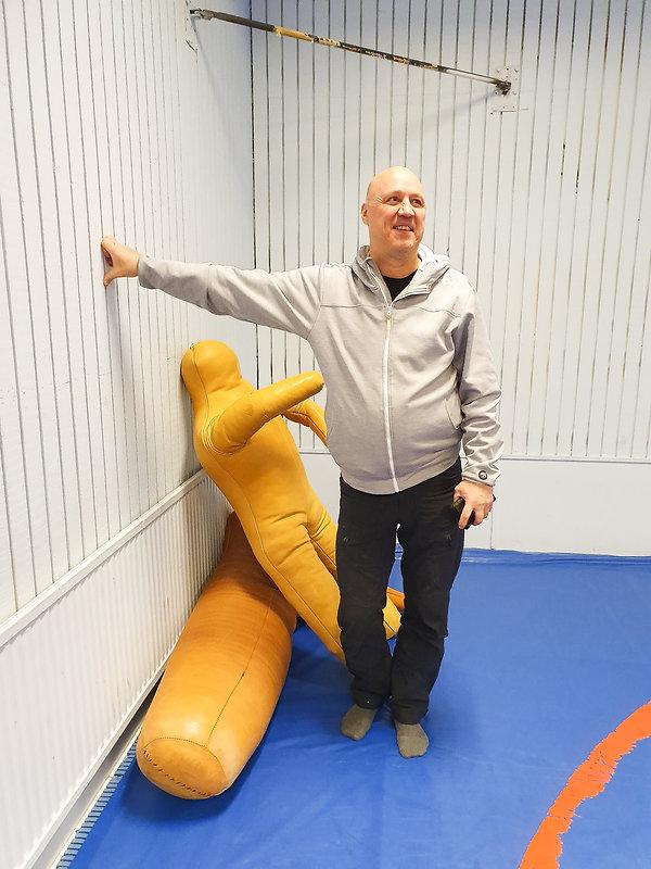 Patrik Larsson står i brottarhallen, han stöttar ena armen mot vägen, ler och tittar ut ur bilden.