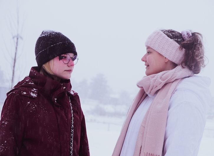 Molly Axelsson till vänster tittar på vännen Linnea Mattsin till höger. Det är snöigt väder.