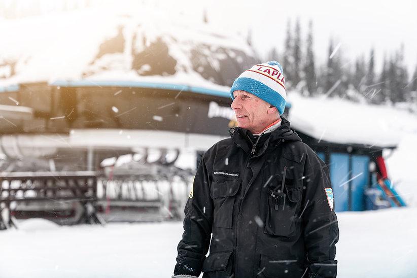 Kjell-Ove iklädd arbetskläder. Han ler och tittar åt sidan, det är snöigt väder och i bakgrunden syns stolliften. Foto: Wesley Overklift