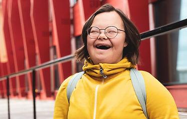 Maja står framför Kunskapethuset. Hon har en gul tröja på sig och skrattar in i kameran
