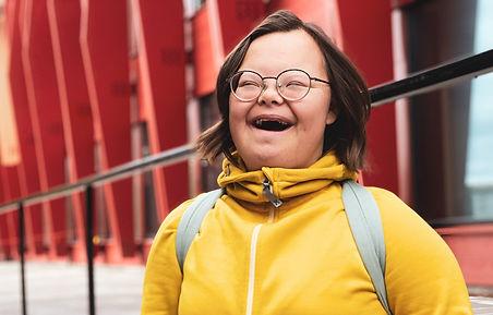 Maja står utanför Kunskapshuset. Hon har en gul tröja på sig och skrattar mot kameran