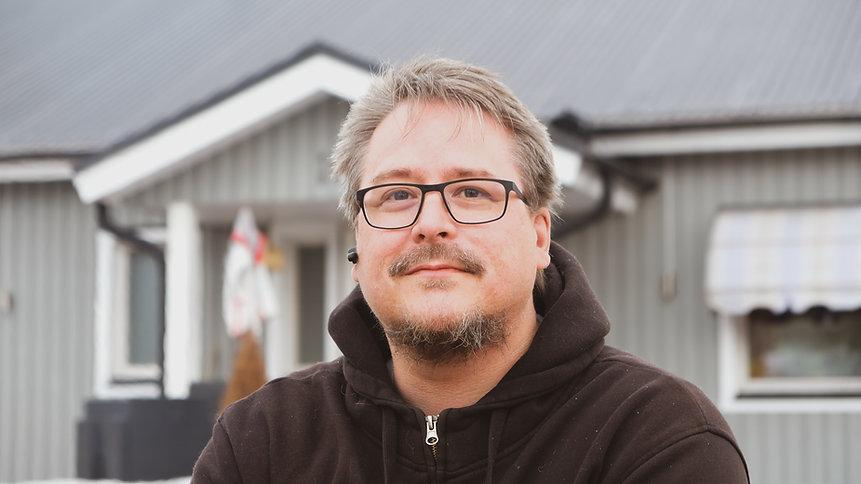 Daniel Willman tittar in i kameran och ler försiktigt, i bakgrunden syns hans grå enplansvilla.