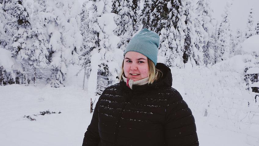 Erika Jannok iklädd nå mössa och svart dunjacka. I bakgrunden syns stängselt på renhagen, och snötyngda granar.