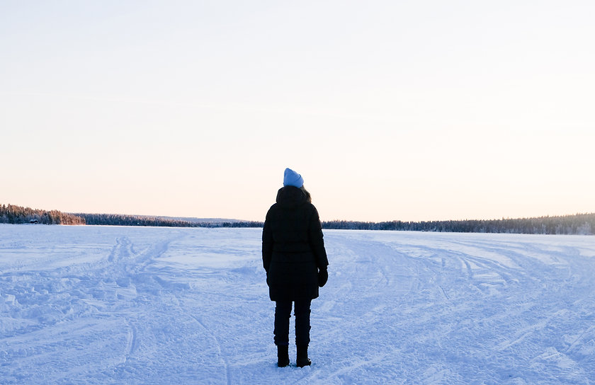 Rebecka står på en frusen sjö. Hon står med ryggen mot kameran.