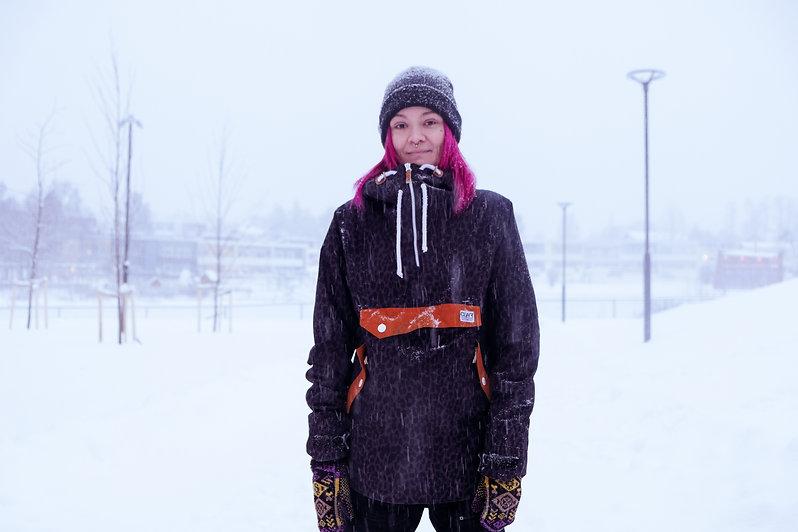 Nadia Hill i står med händerna längs sidan, iklädd svartmönstrad jacka och svart mössa. Det är snöigt väder ute.