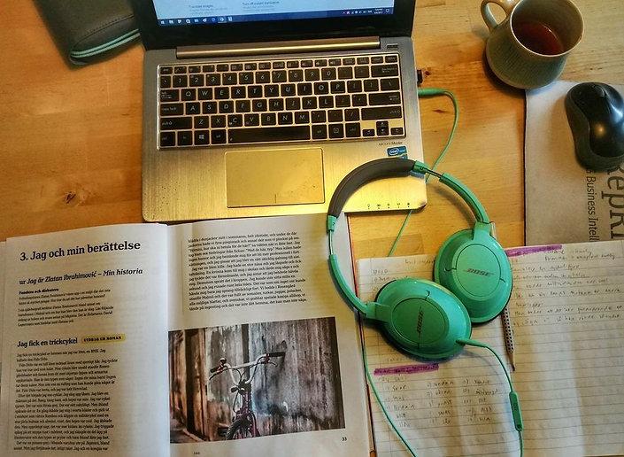 Dator, svenska inlärningsbok och en skrivbok fotad uppifrån. På boken ligger ett par mintgröna hörlurar.