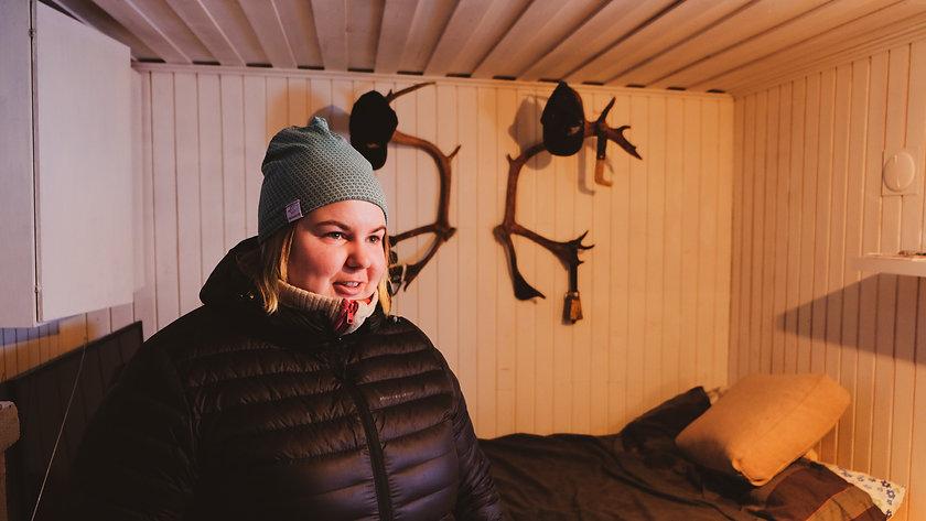 Erika Jannok iklädd blå mössa och svart jacka, hon säger något och titar snett ut i bilden. I bakgrunden syns två stor renhorn uppsatta på väggen.