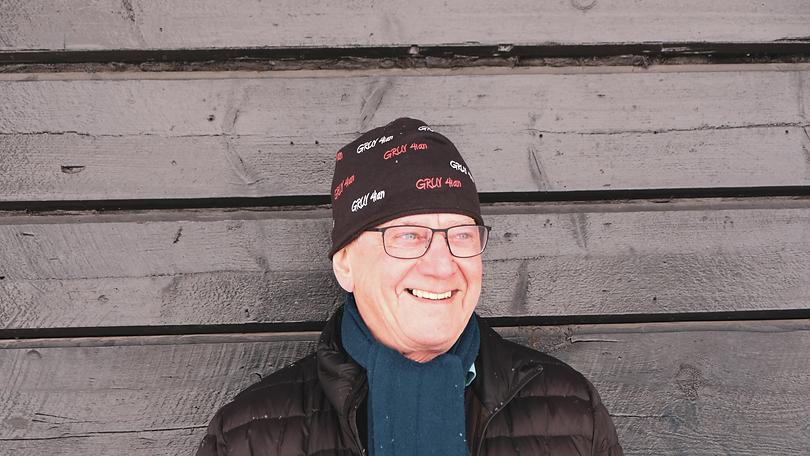 Janne står framför en svartmålad timmervägg. Han bär svart mössa, svart jacka, blå haldsduk, han tittar snett ut ur bild och ler.