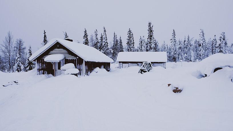 Två älde röda hus, det är snöigt runtomkring och på taken. I bakgrunden smala snöiga granar.