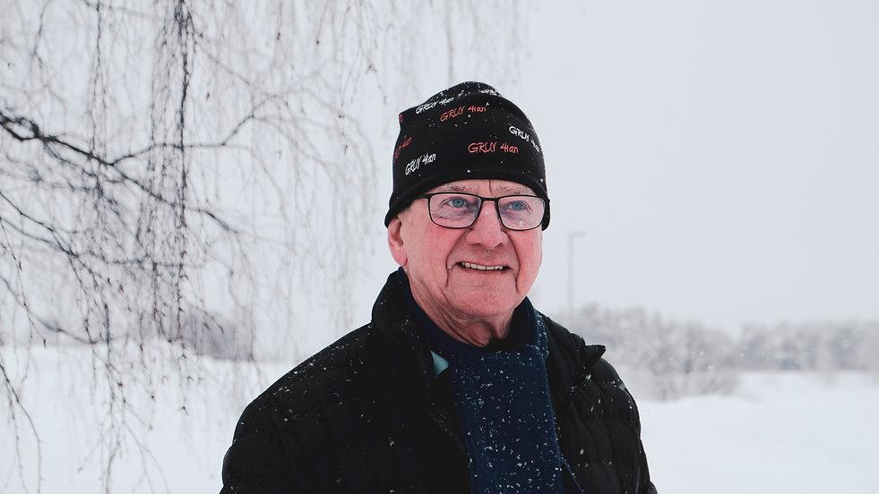 Janne iklädd svart jacka och svart mössa, han bär glas ögon, ler försiktigt och tittar ut ur bilden. Det är snöigt ute.