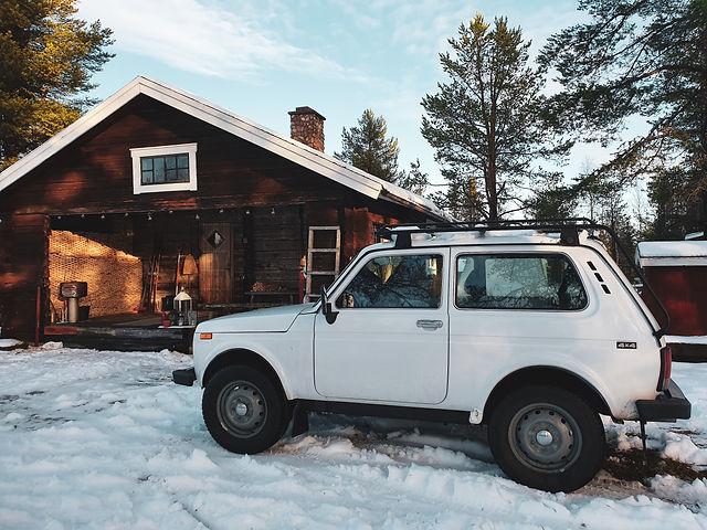 Emmas bruna, robusta timring. Framför står hennes vita bil, en Lada Niva.