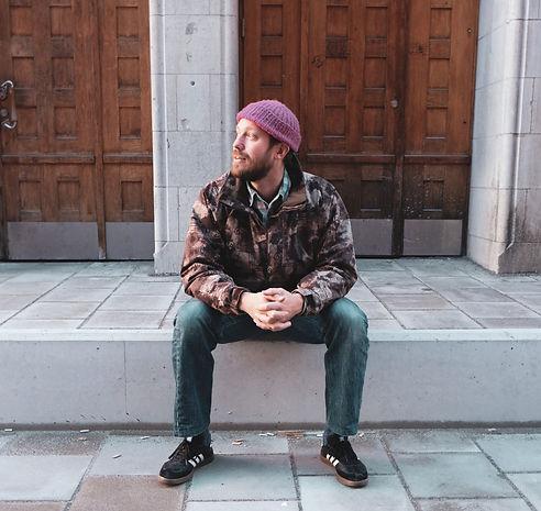 Johan Airijoki sitter på en upphöjd gatsten, framför entrén till Gällivare musem. Han håller ihop sina händer och har huvudet vänt åt sidan.