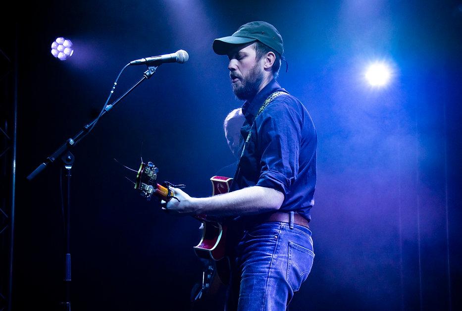 Johan Airijoki står på scenen, sjunger och spelar gitarr. i bakgrunden stå bandkollegan Torbjörn Ömalm, också med gitarr.