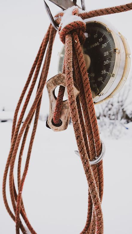Ett lasso som hänger på en vågkrok. Det är lite snö och frost på.