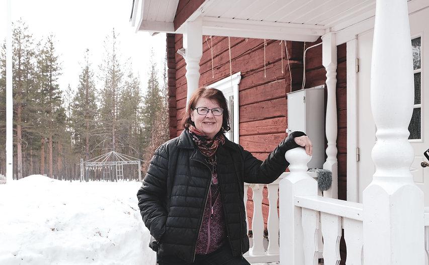 Lena står utanför sitt rödtimrade hus. Hon har på sig en svart jacka och håller handen på broräcket, och ler in i kameran