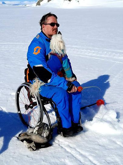 Daniel iklädd blåa vinterkläder sittandes och pimpla. I famnen sitter hans hund.