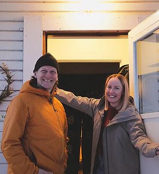 Evelina och Daniel står i dörröppningen utanför sitt hus och ler in i kameran.