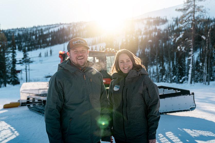 Tobias och Hanna står bredvid varandra och ler in i kameran. I bakgrunden syns en pistmaskin, det är soligt väder ute. Foto: Wesley Overklift