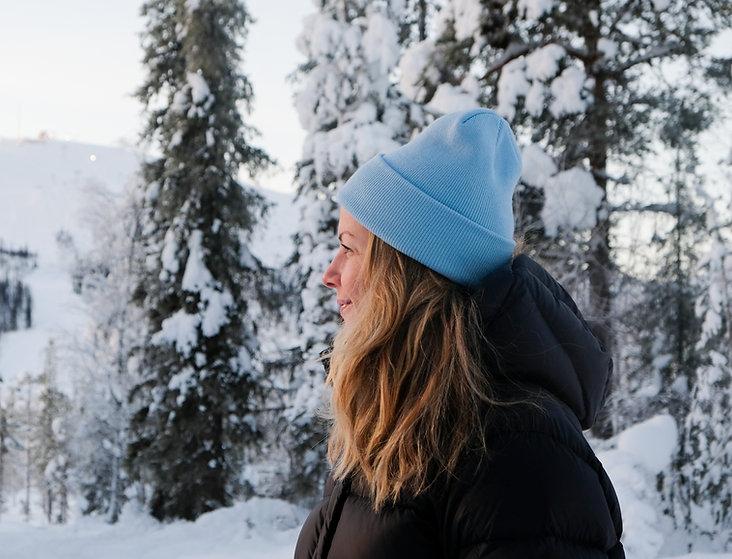 Rebecka fotad från sidan. Hon tittar ur ur bilden och ler lite. Hon bär en svart jacka och en ljusblå mössa.