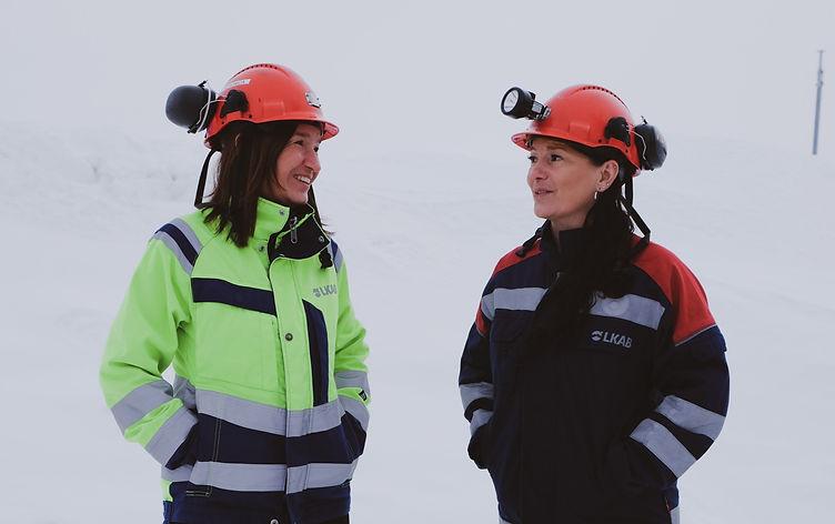Chalotte till vänster i bild, med röd hjälm och varseljacka, Charlotte står till höger i röd hjälm och blå-röd arbetsjacka. De har båda händerna i fickorna, är vända mot varandra och pratar.