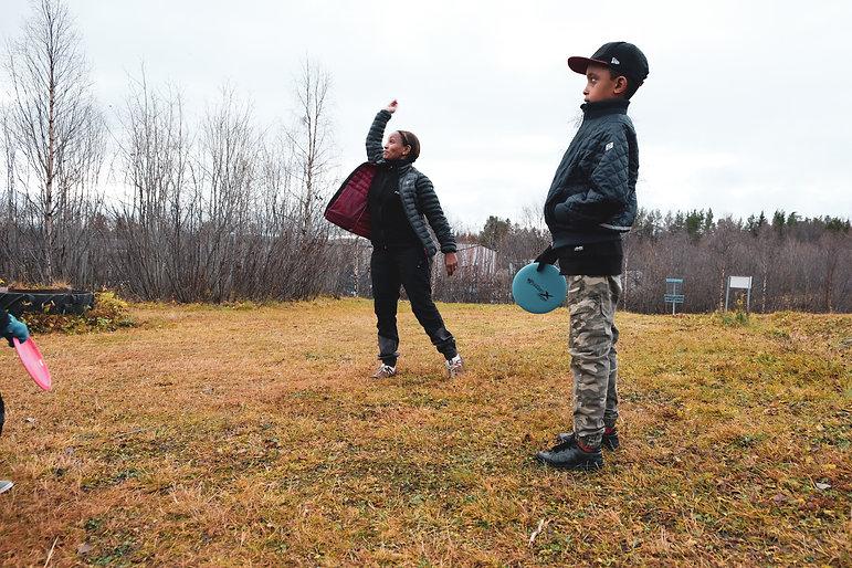 Nigisti kastar iväg en frisbee, Noah tittar på.