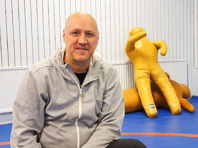 Patrik Larsson sitter i brottarhallen, han ler försiktigt och tittar in i kameran. I bakgrunden syns två brottardockor.