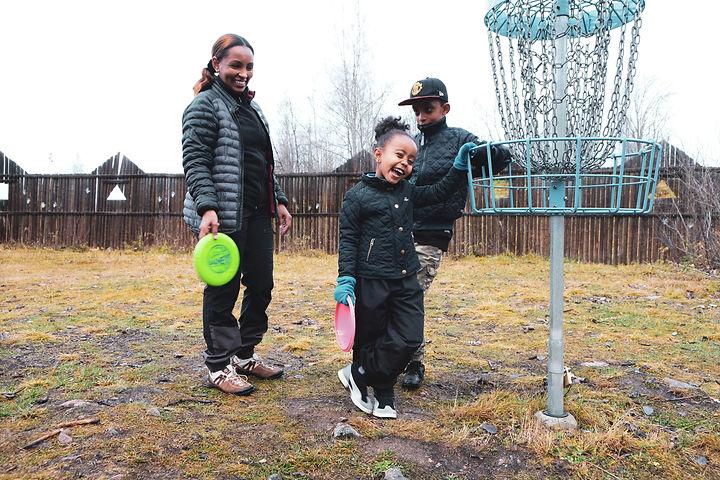 Nigisti med barnen Arsema och Noah, de håller varsinn frisbee i handen.