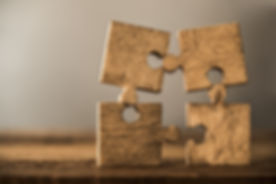 4 Four brown pieces of puzzle stand on wooden table isolated on gray or white background. empty copy