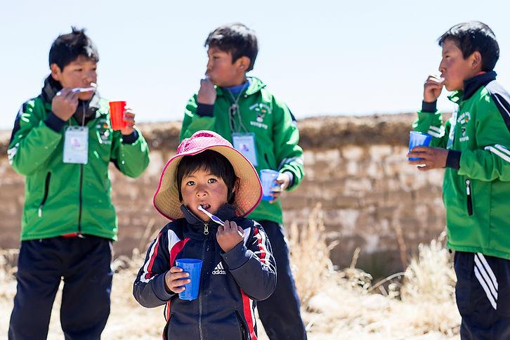 Bolivialaiset koululaiset harjaavat hampaitaan.