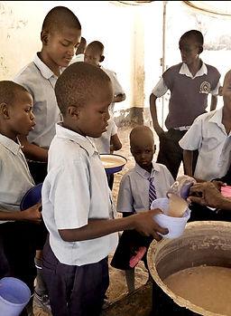 eri-ikäiset pojat odottavat astiat kädessä ruoan jakelua ulkona.jpg