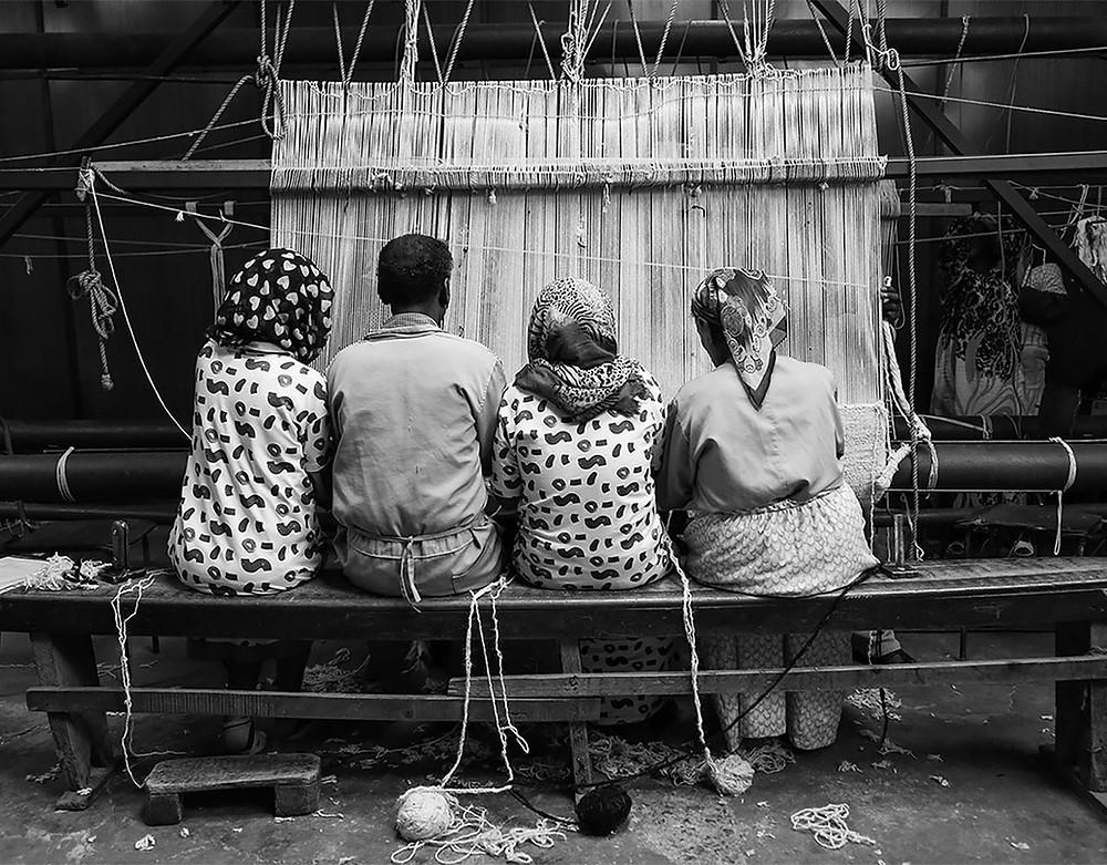 Neljä etiopialaista käsityöläistä solmii mattoa yhdessä penkillä istuen