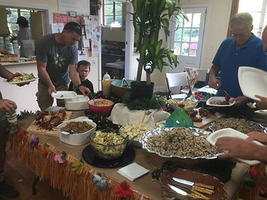 People gather around a potluck table