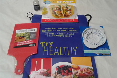 gifts for participants, including cookbooks, a cutting board, a strainer, and a drawstring backpack