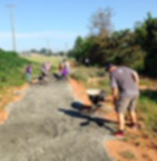 People adding gravel to a trail.