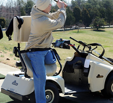Disabled man tees off with assistance fom his golf cart.