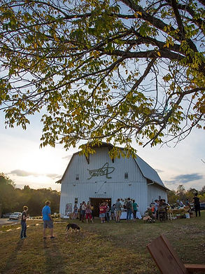 People gather outsid white barn.