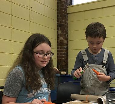 Two kids peel carrots