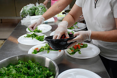 Volunteers put salad on plates.