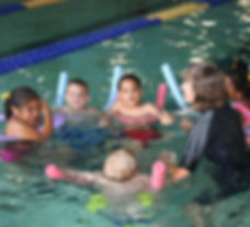 Kids float with noodles in a pool while listening to a swim instructor