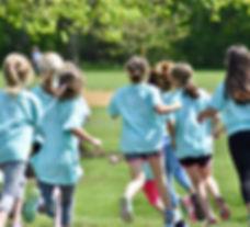 Girls running in the field.
