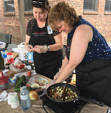 Two women in aprons prepare a veggie stir fry