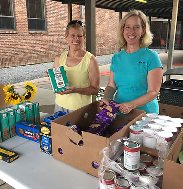 Two women smile behind a display of boxed and canned goods