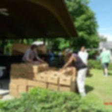 Two men organize boxes of fresh produce.